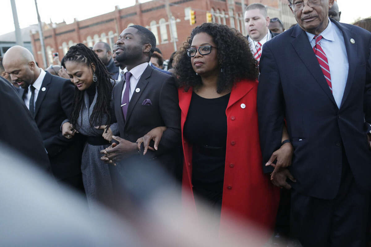 """FILE - In this Sunday, Jan. 18, 2015 file photo, Oprah Winfrey locks arms with David Oyelowo, left, who portrays Martin Luther King Jr. in the movie """"Selma,"""" Ava DuVernay, the director of """"Selma"""" and rapper/actor Common, far left, as they march to the Edmund Pettus Bridge in honor of Martin Luther King Jr., in Selma, Ala. The 50th anniversary of the civil rights marches in Selma and the hit movie, """"Selma,"""" that tells the story are expected to bring thousands of visitors to this historic Alabama city. Visitors can still walk across the bridge where voting rights marchers were beaten in 1965 and visit the churches where they organized the protests. (AP Photo/Brynn Anderson, File)"""