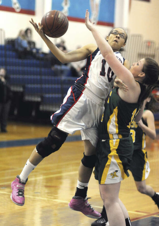 Hour photo/John Nash - Kim Duhart of Brien McMahon, left, loses control of the ball as she goes up for a shot against Trinity Catholic defender Katelyn Spielman during Thursday's game at Kehoe-King Gym in Norwalk.