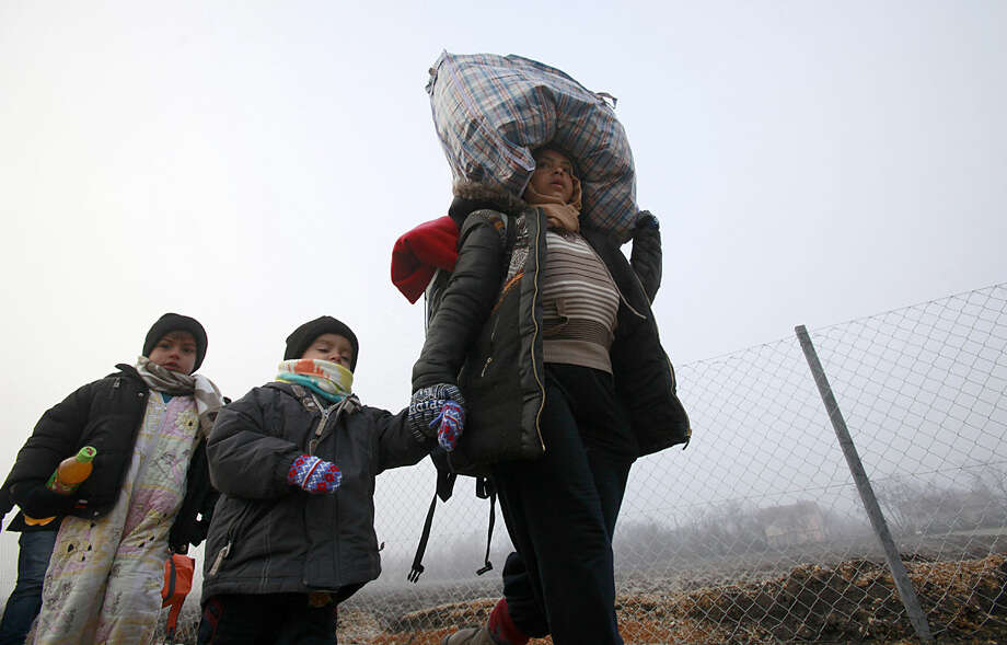 Refugees walk towards the border with Serbia from the transit center for refugees near northern Macedonian village of Tabanovce, while on their journey through the so-called Balkan migrant corridor, Thursday, Jan. 28, 2016. Greek authorities say neighboring Macedonia has stopped Wednesday letting in refugees heading north to central Europe, leaving about 2,600 people stranded on the Greek side of the border. (AP Photo/Boris Grdanoski)