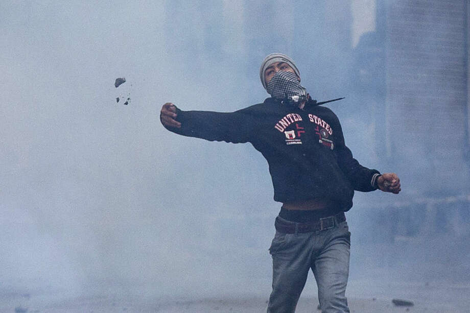 A Kashmiri Muslim protester pelts stones at Indian policemen amid tear gas smoke during a protest in Srinagar, Indian controlled Kashmir, Friday, Jan. 29, 2016. Police fired teargas and rubber bullets to disperse Kashmiris who gathered after Friday afternoon prayers to protest against Indian control over a part of the disputed region. (AP Photo/Dar Yasin)