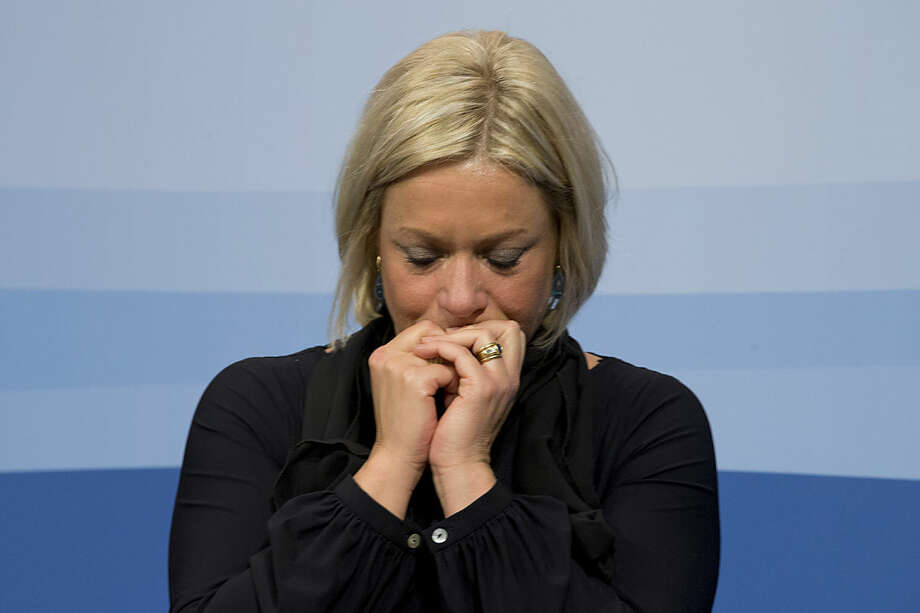 Defense Minister Jeanine Hennis-Plasschaert reacts to a loud crackling sound from the microphone amplifier when explaining the cabinet decision to extend its campaign of Dutch air strikes from Iraq into Eastern Syria during a press conference in The Hague, Netherlands, Friday, Jan. 29, 2016. (AP Photo/Peter Dejong)