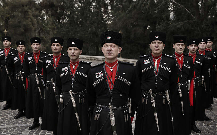 In this Monday, Jan. 11, 2016 photo, Circassian guards pose for a photograph outside Basman Palace, in Amman, Jordan. Circassian guards, who have served Jordan's kings since the founding of the monarchy, still adhere to their ancient traditions, such as donning an incongruous cold weather uniform of black wool hats, red capes and leather boots in this desert climate. (AP Photo/Nariman El-Mofty)