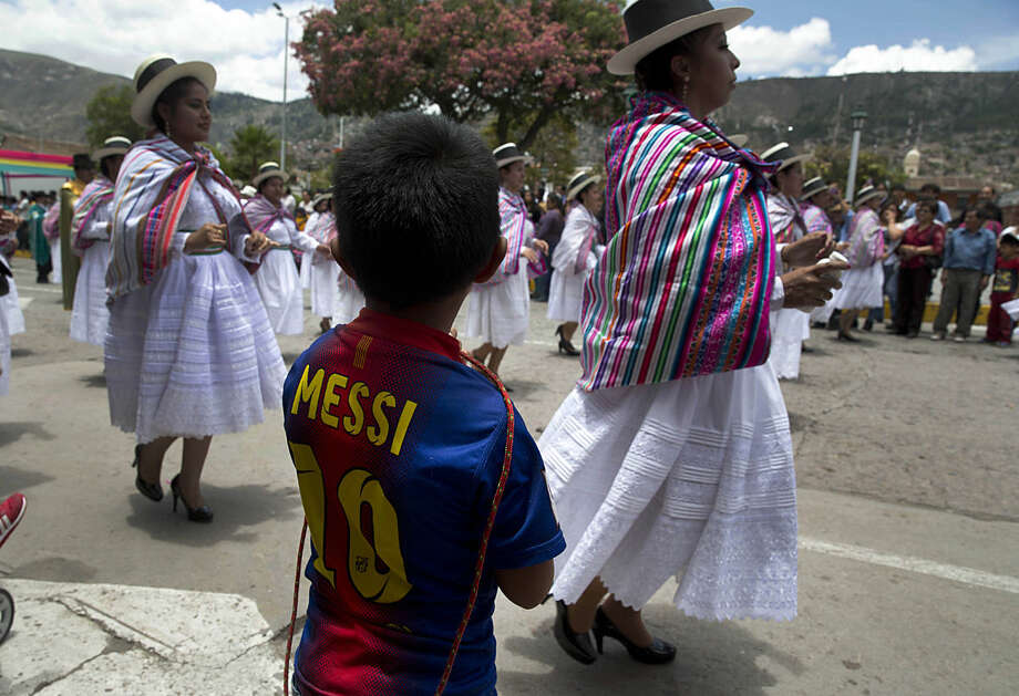 A boy wearing Barcelona soccer star Lionel Messi T-shirt, stands while Andean women in traditional dress dance during the carnival in Ayacucho, Peru, Thursday, Jan. 28, 2016. The carnival in the Andean region of Peru begins at the same the time farmers plant their crops. (AP Photo/Martin Mejia)