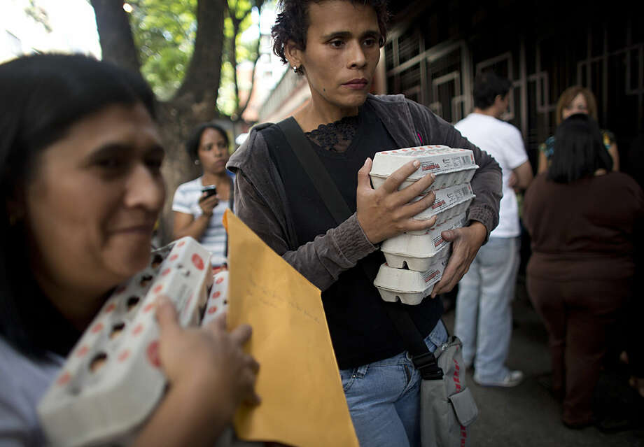 People carry boxes of eggs after buying them at government regulated prices as they walk on a street in Caracas, Venezuela, Wednesday, Jan. 27, 2016. There is currently a shortage of eggs in the country. In a note published last Friday, the International Monetary Fund Western Hemisphere Director Alejandro Werner said inflation would more than double in the economically struggling South American country in 2016, reaching 720 percent. (AP Photo/Ariana Cubillos)