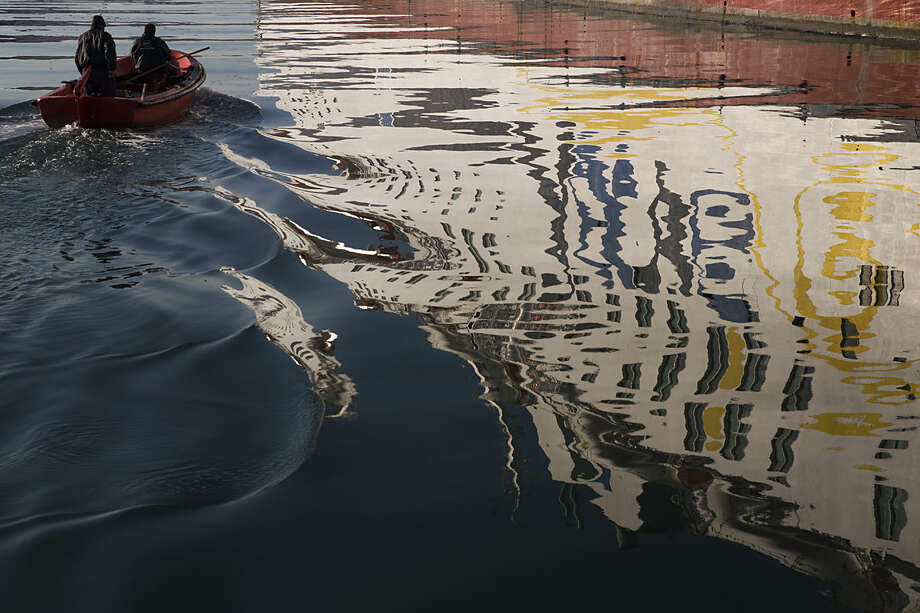 An immobilized ferry is reflected in the sea as a small boat sails in the Athens' main port of Piraeus, Friday, Jan. 29, 2016. Greek seamen have extended an anti-austerity 48-hour strike for a further 48 hours, halting island ferry services, as bailout-reliant Greece is planning to drastically overhaul its troubled pension and social security system, among other reforms demanded by international creditors. (AP Photo/Petros Giannakouris)