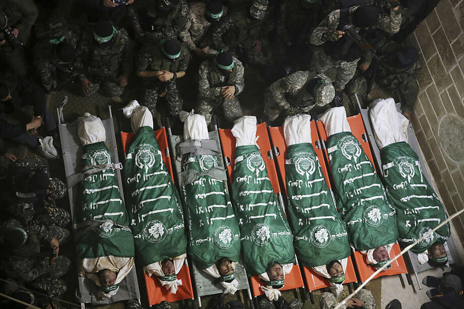 Palestinian militants from the Izzedine al-Qassam Brigades, a military wing of Hamas, pray by the bodies of seven Hamas member killed repairing a tunnel during their funeral at a mosque in Gaza City, Friday, Jan. 29, 2016. Hamas said Thursday that 11 militants were repairing the tunnel to fix damage sustained from heavy rainfall. The tunnel collapsed killing seven, while the rest were rescued, it said. Hamas has built a sophisticated network of tunnels that it has used to penetrate Israel to carry out attacks on civilians and soldiers. Israel destroyed dozens of the tunnels in the war with the militant group in Gaza in 2014. (AP Photo/Adel Hana)