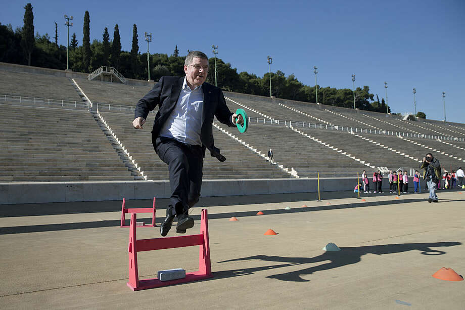 IOC President Thomas Bach, jumps over a hurdle while he is playing with children during his visit at the marble Panathenian Stadium, venue of the first modern Olympics in 1896, in Athens on Friday, Jan, 29, 2016. Bach who is in Greece on a three-day visit said Thursday that a group of refugee athletes will march together in the opening ceremony of the Olympics in Rio de Janeiro in a symbol of hope for the world's migrants. (AP Photo/Petros Giannakouris)