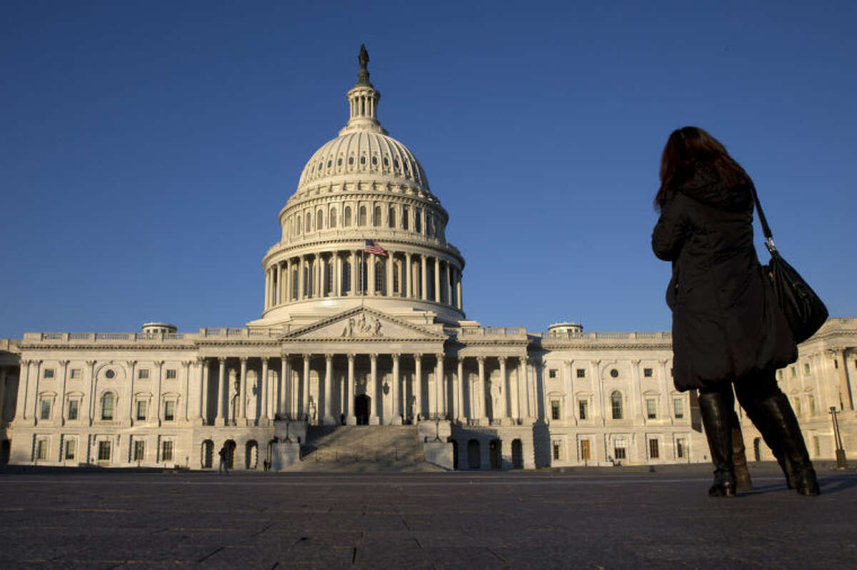 FILE - In this Dec. 31, 2013, file photo, a woman looks at the U.S. Capitol in Washington. After last fall?'s tumultuous, bitterly partisan debt ceiling and government shutdown battles, a sense of fiscal fatigue seems to be setting in among many Washington policymakers as President Barack Obama prepares for his fifth State of the Union address later this month. (AP Photo/Jacquelyn Martin, File)