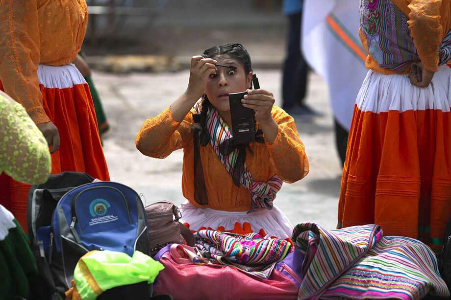 An Andean woman in traditional dress, applies mascara before the carnival in Ayacucho, Peru, Thursday, Jan. 28, 2016. The carnival in the Andean region of Peru begins at the same the time farmers plant their crops. (AP Photo/Martin Mejia)