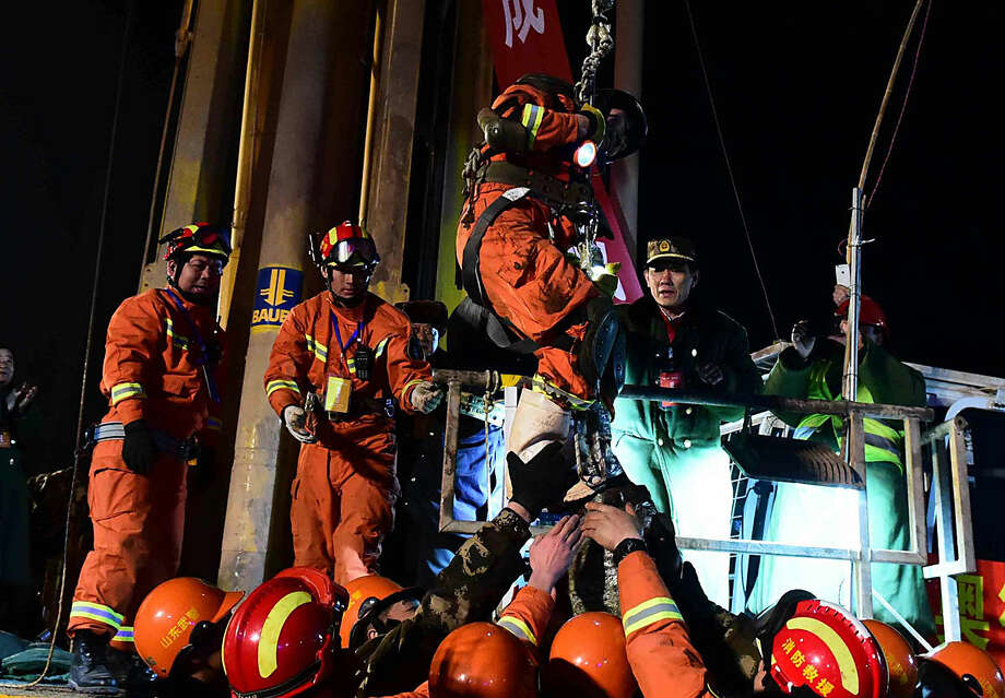 The first miner, is lifted from a collapsed mine in Pingyi, east China's Shandong Province, Friday evening Jan. 29, 2016. Chinese state media say two miners have been rescued from a collapsed mine after spending 36 days trapped underground. Efforts continued Friday to reach the remaining two people in the mine in east China's Shandong province. The gypsum mine collapsed on Christmas Day, killing one and leaving 13 others missing. In the days that followed, rescuers detected four survivors 200 meters (660 feet) below the surface. (Guo Xulei/Xinhua via AP) CHINA OUT