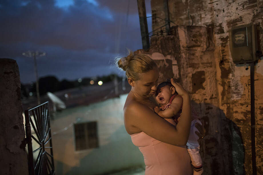 Gleyse Kelly da Silva, 27, holds her daughter Maria Giovanna, who was born with microcephaly, outside their house in Recife, Pernambuco state, Brazil, Wednesday, Jan. 27, 2016. Brazilian officials still say they believe there's a sharp increase in cases of microcephaly and strongly suspect the Zika virus, which first appeared in the country last year, is to blame. The concern is strong enough that the U.S. Centers for Disease Control and Prevention this month warned pregnant women to reconsider visits to areas where Zika is present. (AP Photo/Felipe Dana)