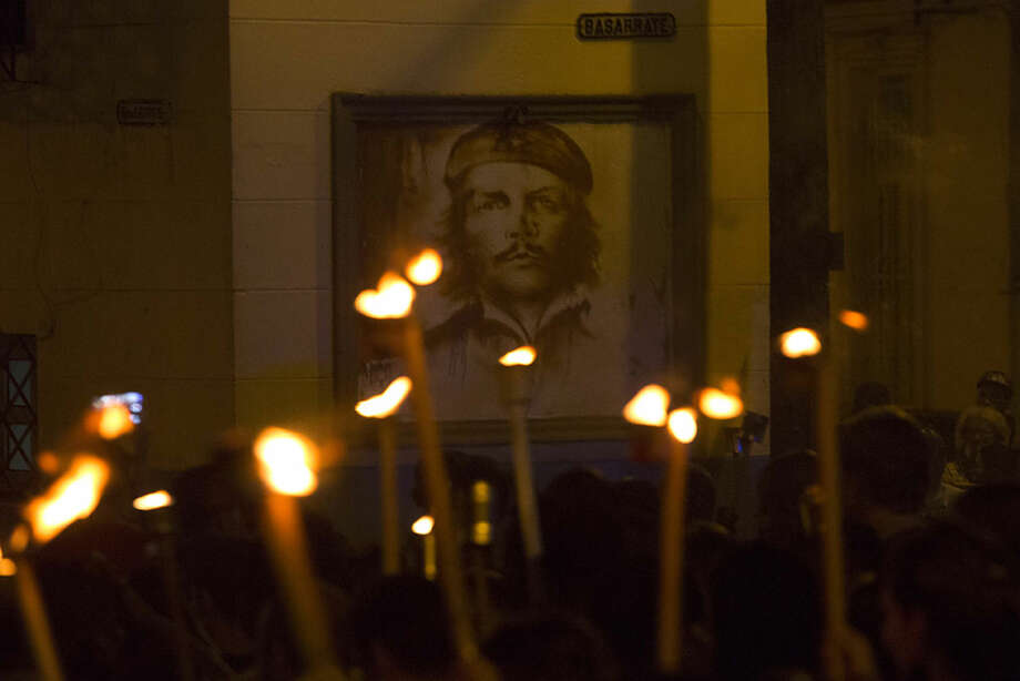 People march with torches beside a portrait of rebel hero Che Guevara in a procession, marking the 163rd anniversary of the birth of Cuba's national independence hero Jose Marti, in Havana, Cuba, Wednesday, Jan. 27, 2016. Through his writings and political activity, Marti became a symbol for Cuba's bid for independence against Spain in the 19th century. (AP Photo/Desmond Boylan)