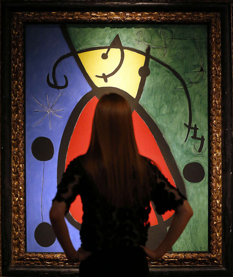 A woman is silhouetted in front of Joan Miro's painting, 'Woman and Bird in the night', at the Christie's auction house in London, Friday, Jan. 29, 2016. Christie's the Art of the Surreal Evening sale takes place on Feb. 2, 2016. The estimated price for Miro's painting is euro 4,1-6,7 million, $ 4,4-7,3 million. (AP Photo/Frank Augstein)