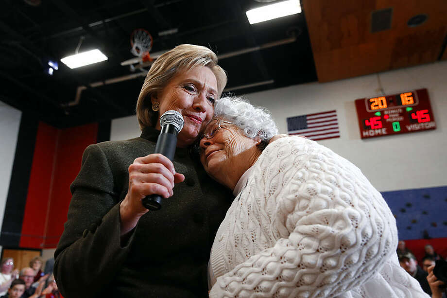 Democratic presidential candidate Hillary Clinton, left, hugs Annette Bebout, 73, of Newton, during a campaign event at Berg Middle School, Thursday, Jan. 28, 2016 in Newton, Iowa. Bebout told her story of how she lost her home to the audience. (AP Photo/Paul Sancya)