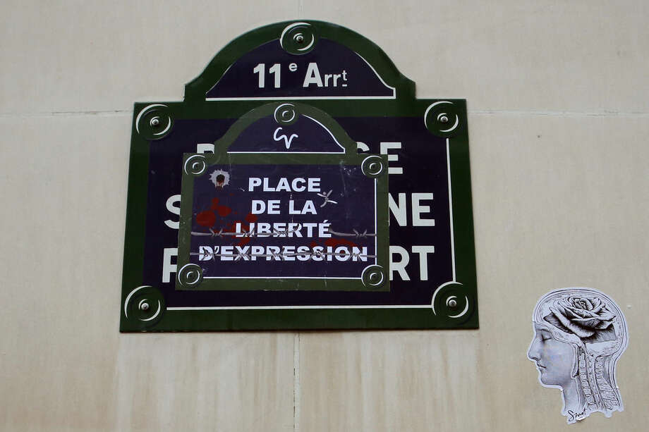 "The street sign near the offices of French satirical publication Charlie Hebdo, where Brothers, Said and Cherif Kouachi killed people in a terror attack is replaced with a poster reading ""Place of the freedom of expression"", in Paris, Tuesday Jan. 20, 2015. Brothers, Said and Cherif Kouachi and their friend, Amedy Coulibaly, killed 17 people at the satirical newspaper Charlie Hebdo, a kosher grocery and elsewhere last week. (AP Photo/Francois Mori)"
