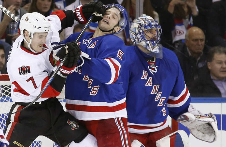 Ottawa Senators center Kyle Turris (7) fends off New York Rangers defenseman Dan Girardi (5) as Rangers goalie Henrik Lundqvist watches other players during the second period of an NHL hockey game at Madison Square Garden in New York, Tuesday, Jan. 20, 2015. (AP Photo/Kathy Willens)
