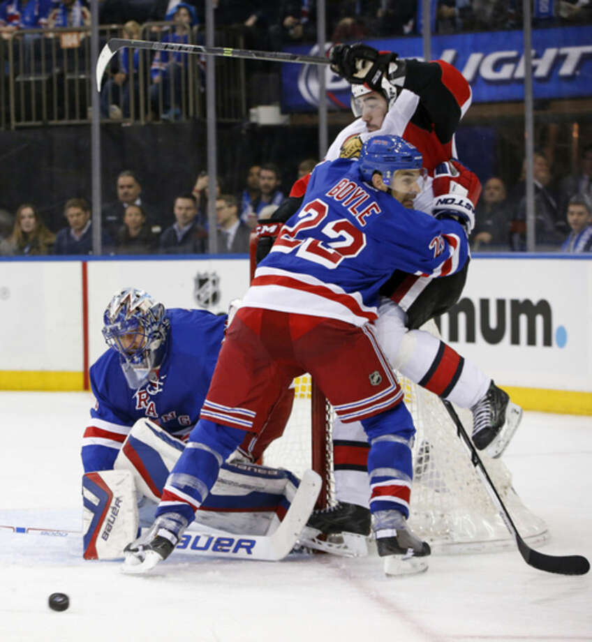 New York Rangers defenseman Dan Boyle (22) fends off Ottawa Senators center Mika Zibanejad (93), of Sweden, as Rangers goalie Henrik Lundqvist (30), of Sweden, makes a save in the third period of an NHL hockey game at Madison Square Garden in New York, Tuesday, Jan. 20, 2015. (AP Photo/Kathy Willens)