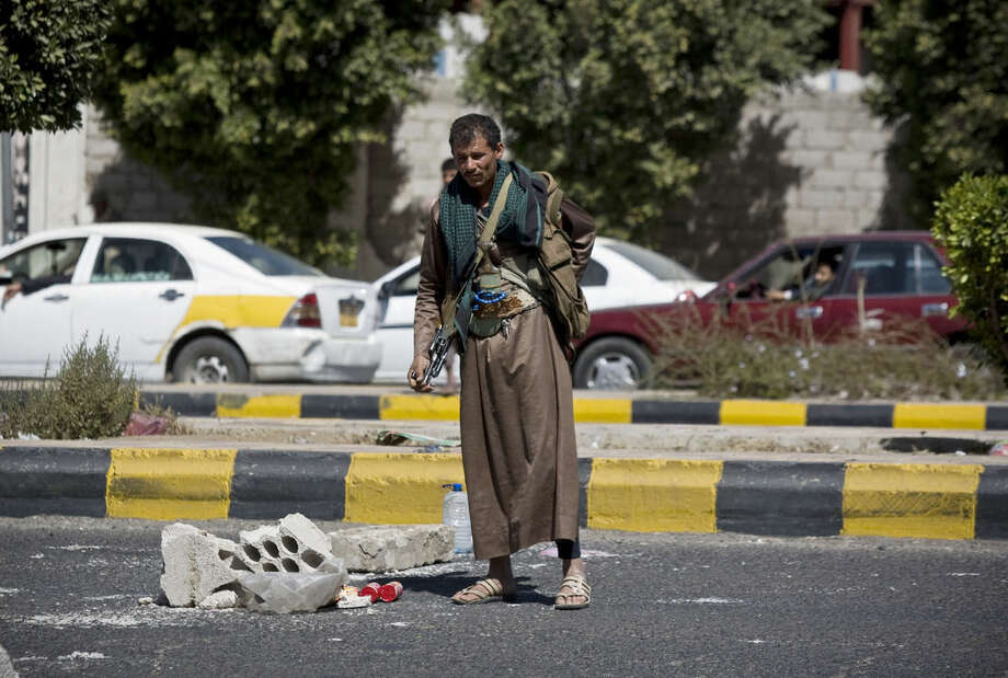 A Houthi Shiite Yemeni stands guard at a street leading to the presidential palace in Sanaa, Yemen, Wednesday, Jan. 21, 2015. Authorities in southern Yemen have closed the country's second-largest airport there in protest over the Shiite rebels' power grab in the capital, Sanaa, which has plunged the nation deeper into chaos and threatens to fracture the country. (AP Photo/Hani Mohammed)