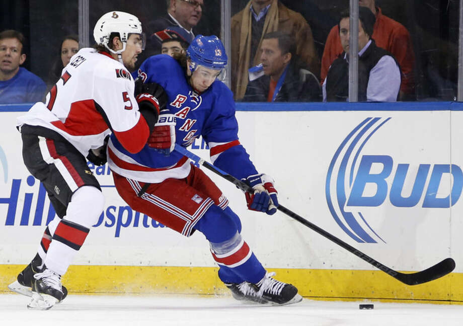 Ottawa Senators defenseman Cody Ceci (5) checks New York Rangers right wing Kevin Hayes (13) during the first period of an NHL hockey game at Madison Square Garden in New York, Tuesday, Jan. 20, 2015. (AP Photo/Kathy Willens)