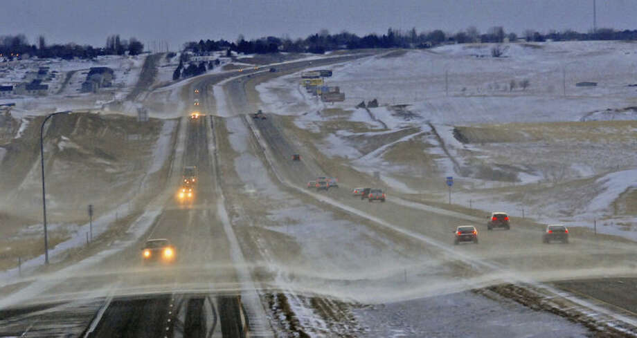 Traffic moves slower than usual on I-94 west of Mandan, N.D. shortly after sunrise as high crosswinds and blowing snow reduced visibility and made for hazardous driving conditions and road closures, Thursday, Jan. 16, 2014. (AP Photo/The Bismarck Tribune, Tom Stromme)