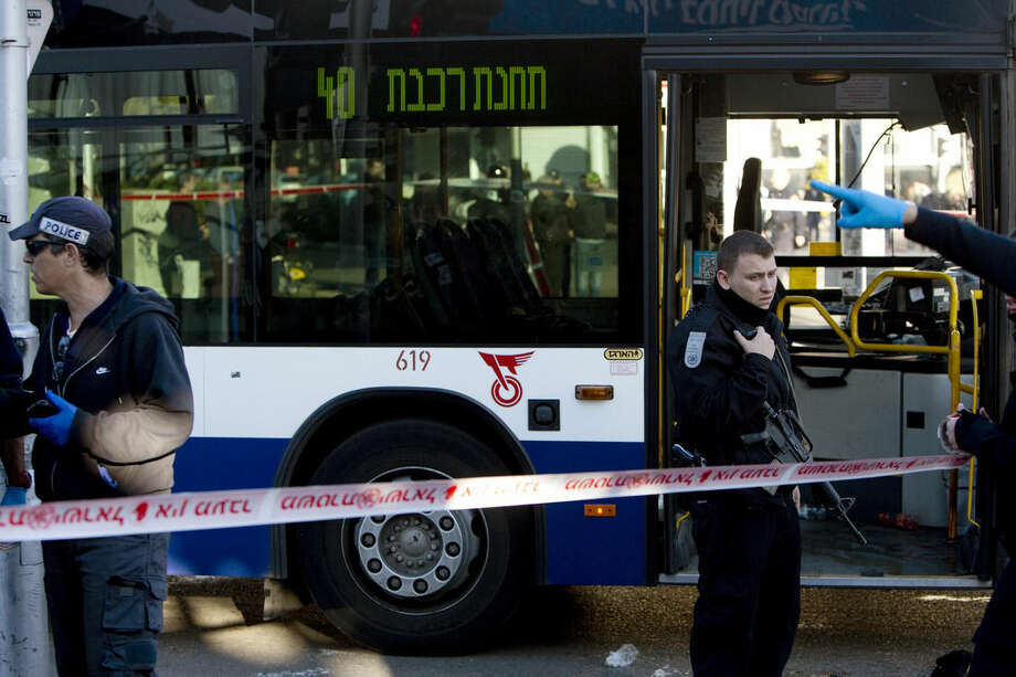 """Israeli police officers secure the scene of a stabbing attack in Tel Aviv, Israel, Wednesday, Jan. 21, 2015. A Palestinian man stabbed nine people, injuring several seriously, on a bus in central Tel Aviv before he was chased down, shot and arrested, Israeli police said Wednesday, describing the assault as a """"terror attack"""" in the latest in a spate of violence, the worst Israel has seen in almost a decade. (AP Photo/Oded Balilty)"""