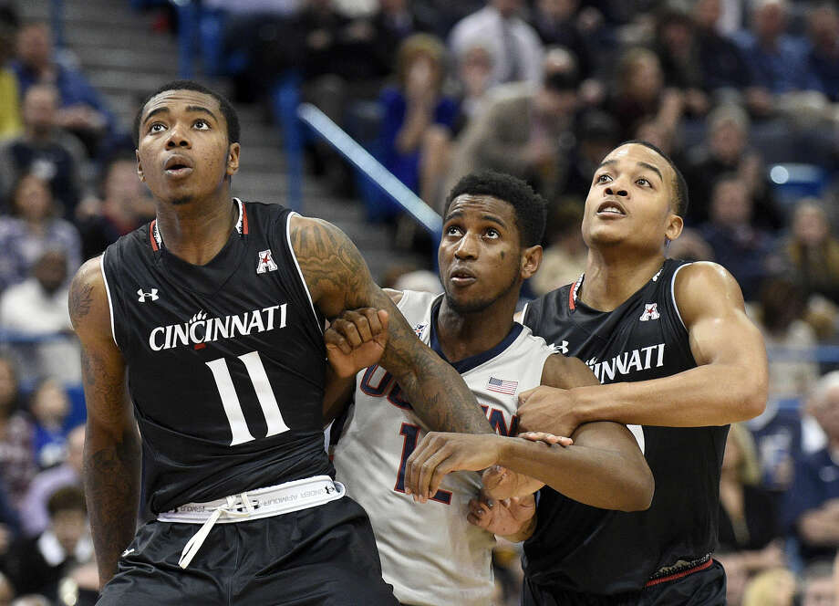 Cincinnati's Gary Clark (11) and Troy Caupain box out Connecticut's Kentan Facey (12) during the first half of an NCAA college basketball game in Hartford, Conn., on Thursday, Jan. 28, 2016. Cincinnati won 58-57. (AP Photo/Fred Beckham)