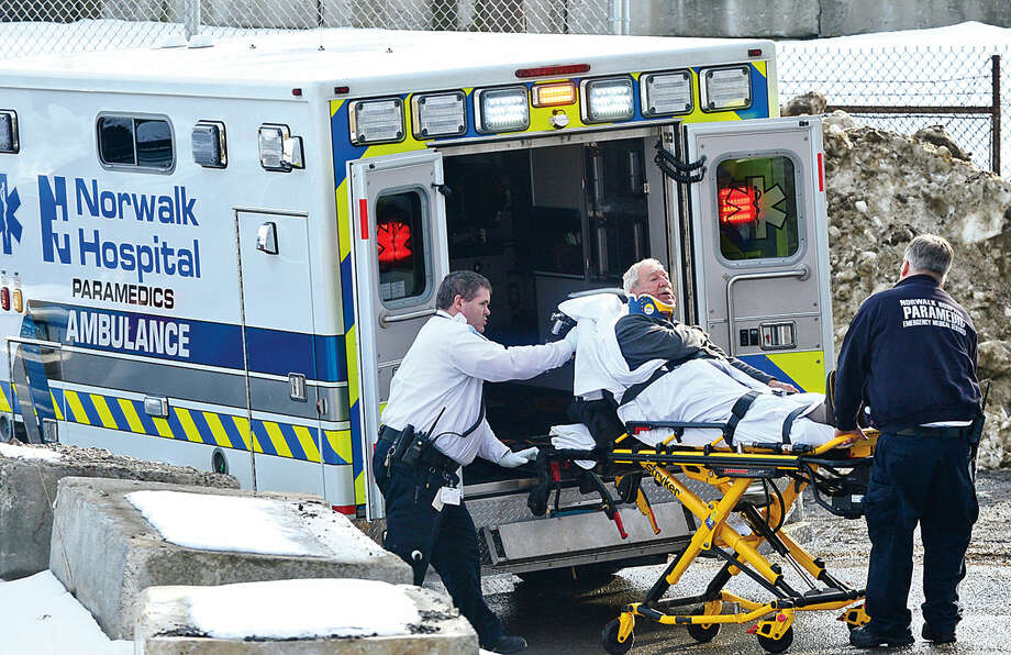 Hour photo / Erik Trautmann A man is transported to Norwalk Hospital after a Metro North train traveling North on the Danbury line struck the vehicle he was driving at Railroad Place near Commerce St Tuesday afternoon.
