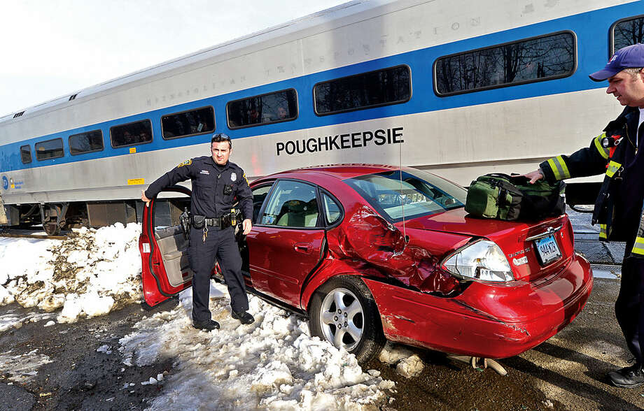 Hour photo / Erik Trautmann Emergency personnel respond to an accident scene where Metro North train traveling North on the Danbury line struck a vehicle at Railroad Place near Commerce St Tuesday afternoon.