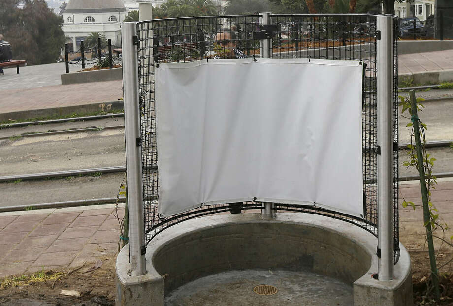 A woman looks at the fencing of an outdoor urinal at a San Francisco MUNI streetcar stop across from Dolores Park in San Francisco on Thursday, Jan. 28, 2016. The city's iconic Dolores Park is now home to the city's first open-air urinal, the latest move to combat the destructive scourge of public urination in the City by the Bay. (AP Photo/Jeff Chiu)