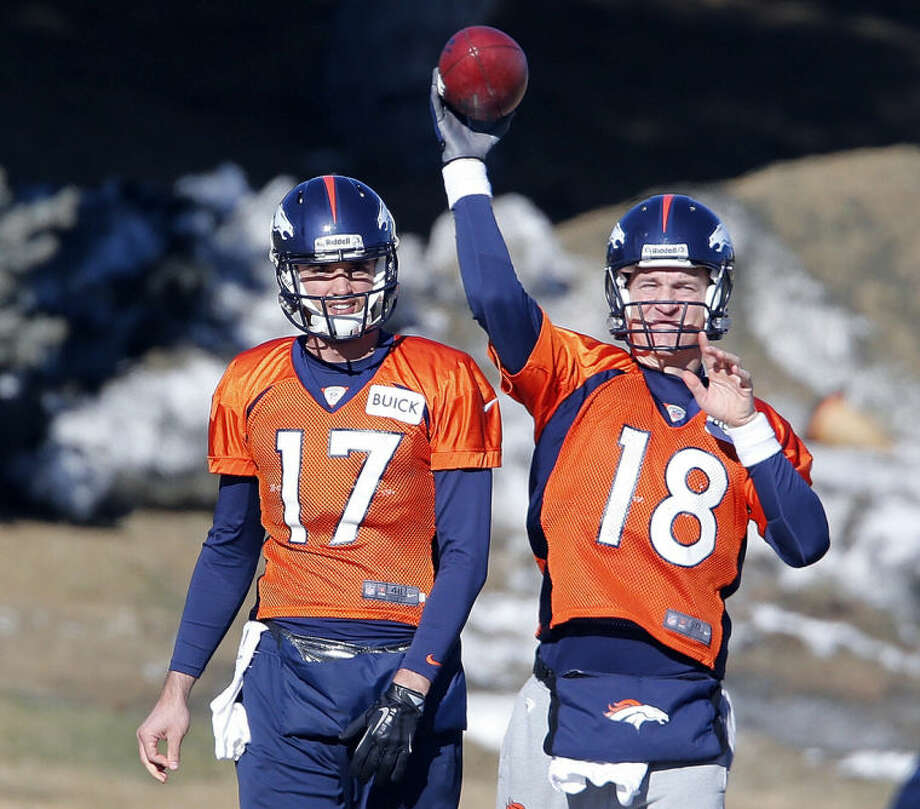 Denver Broncos quarterback Peyton Manning (18) throws a pass as backup quarterback Brock Osweiler (17) looks on during NFL football practice at the team's training facility in Englewood, Colo., on Friday, Jan. 17, 2014. The Broncos are scheduled to host the New England Patriots on Sunday for the AFC championship. (AP Photo/Ed Andrieski)