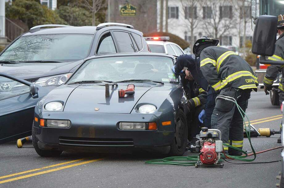Hour Photo/Alex von Kleydorff Norwalk Firefighters work to remove a driver side door and extricate the driver involved on a multi vehicle accident on East Ave Wednesday