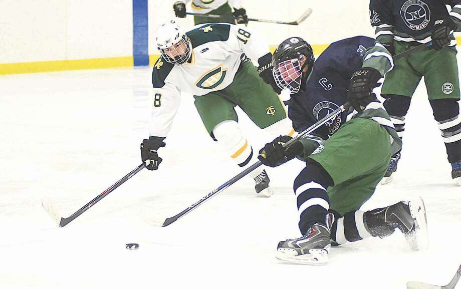 Norwalk-McMahon's Matt Cavanagh, right, goes to a knee while playing the puck as a Trinity Catholic player moves in to defend during Wednesday's FCIAC boys hockey game at Terry Conners Rink in Stamford.