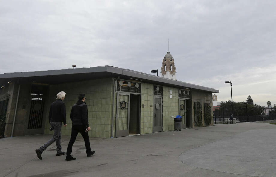 Two men walk in front of a public restroom facility at Dolores Park in San Francisco, Thursday, Jan. 28, 2016. The popular San Francisco park this week has reopened with renovations and the new public urinal, the latest move to combat public urination in the city. (AP Photo/Jeff Chiu)