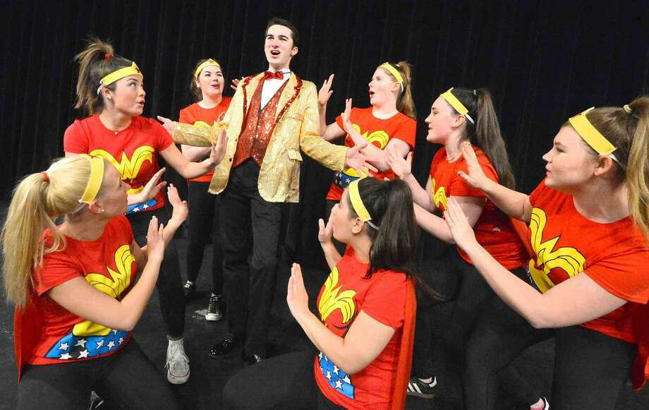 "Daniel Glynn surrounded by his Wonderettes: Brittany Everitt, Annabel Randolf, Eillis Garcia, Julia Siewert, Caroline Casey, Emily Ettie and Tori Baggio in Wilton High School's Senior Class Show ""Superheroes."""