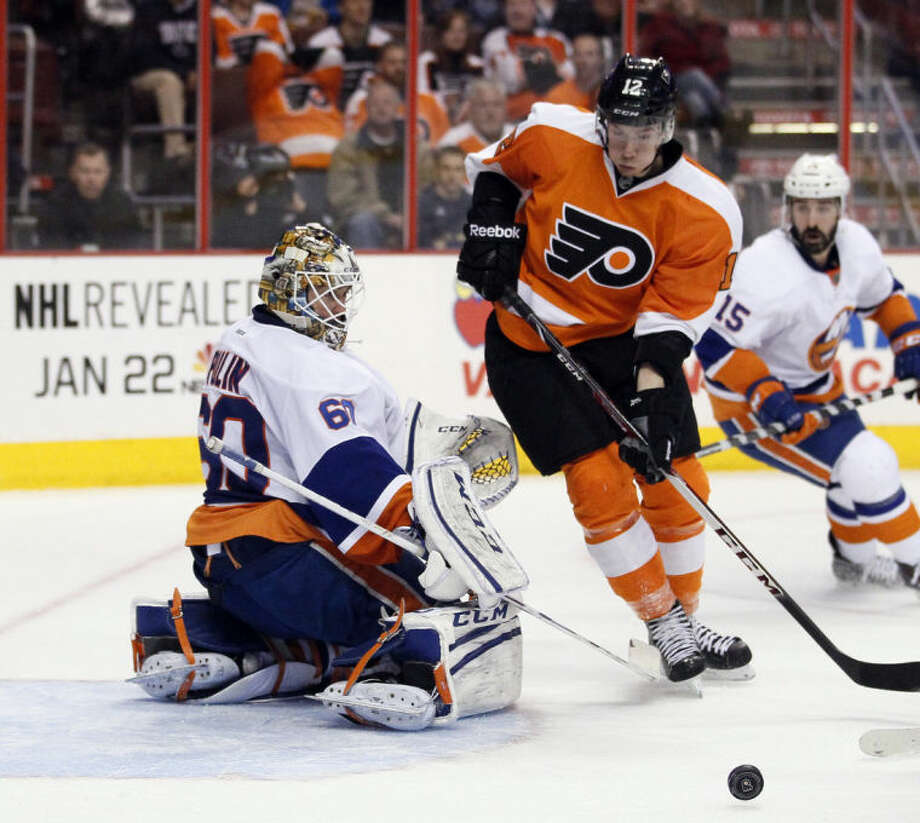 New York Islanders goalie Kevin Poulin, left, and Philadelphia Flyers' Michael Raffl, right, watch the puck during the second period of an NHL hockey game, Saturday, Jan. 18, 2014, in Philadelphia. (AP Photo/Tom Mihalek)