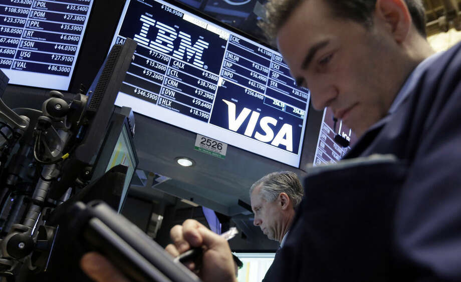 Trader Gregory Rowe, right, stops at the post that handles IBM on the floor of the New York Stock Exchange, Wednesday, Jan. 21, 2015. IBM's fourth-quarter net income dropped 11 percent as revenue in most categories continued to decline, and its outlook for the year disappointed investors. (AP Photo/Richard Drew)