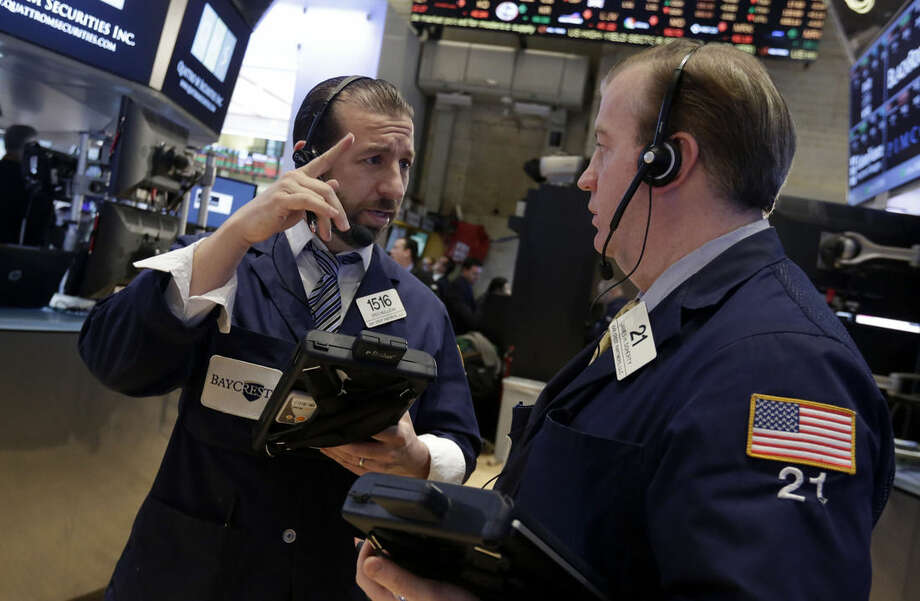 Traders Greg Mulligan, left, John Doherty work on the floor of the New York Stock Exchange Wednesday, Jan. 21, 2015. The U.S. stock market is mixed in early trading after two straight days of gains. (AP Photo/Richard Drew)
