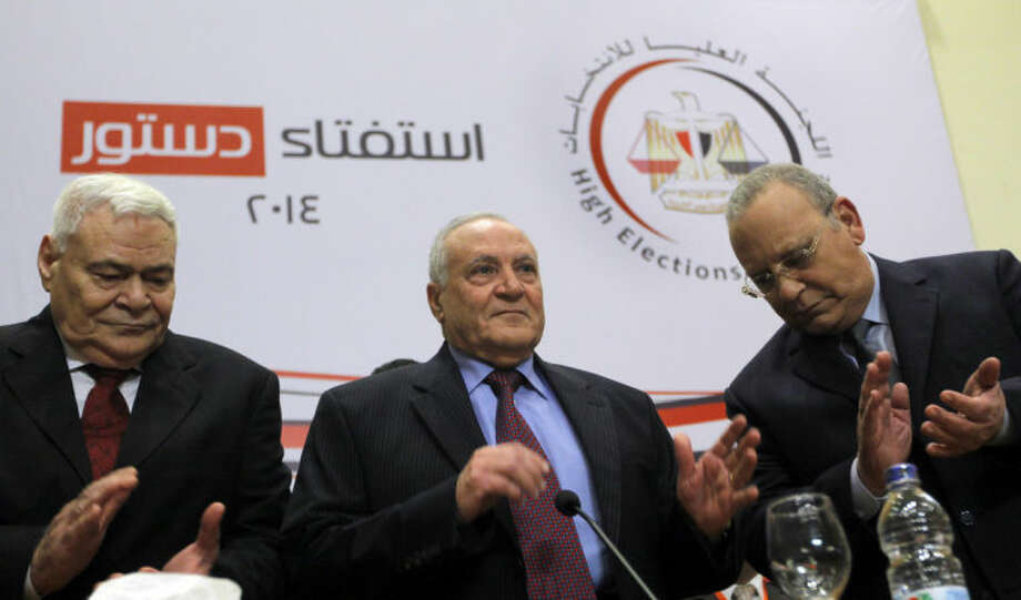"Judge Nabil Salib, head of Egypt's High Election Commission, center, is greeted by other members as he prepares to announce the voting results of a referendum on Egypt's military-backed constitution, in Cairo, Egypt, Saturday, Jan. 18, 2014. Voters overwhelmingly supported Egypt's military-backed constitution in a two-day election, with 98.1 percent supporting it in the first vote since a coup toppled the country's president, the election commission said Saturday. In the lead up to the vote, police arrested those campaigning for a ""no"" vote on the referendum, leaving little room for arguing against the document. (AP Photo/Amr Nabil)"