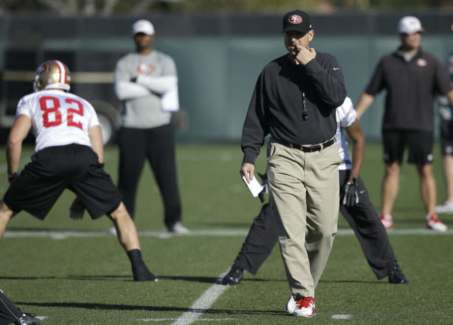 San Francisco 49ers coach Jim Harbaugh, right, walks on the field prior to an NFL football practice in Santa Clara, Calif., Friday, Jan. 17, 2014. The 49ers are scheduled to play the Seattle Seahawks for the NFC championship Sunday. (AP Photo/Ben Margot)