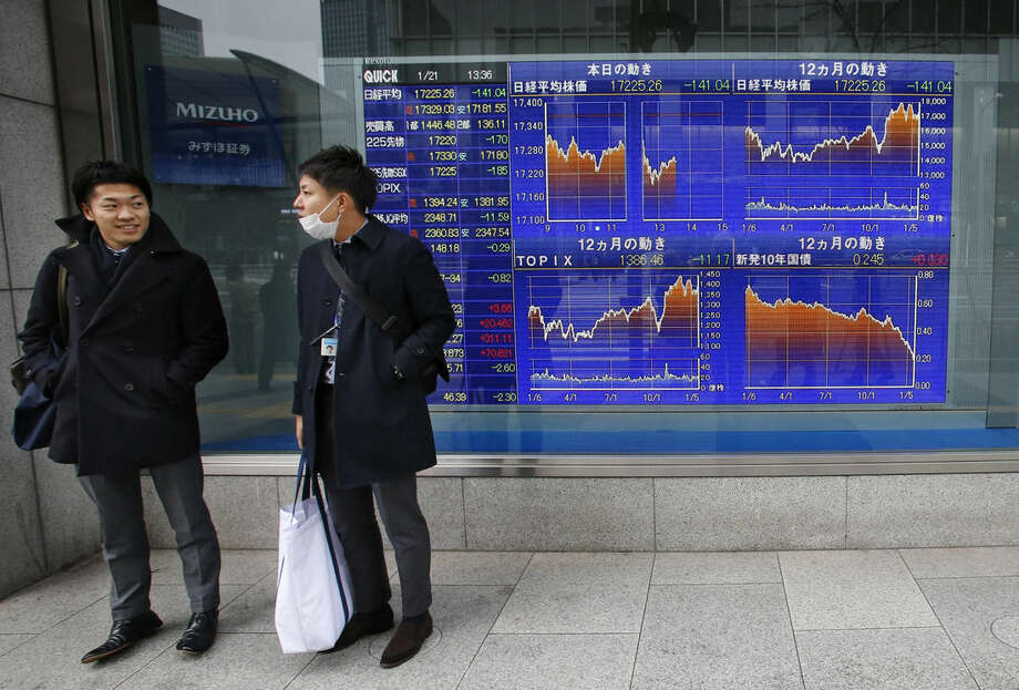 Men wait to cross a street in front of an electronic stock indicator in Tokyo, Japan, Wednesday, Jan. 21, 2015. Most Asian stock markets rose Wednesday as investors anticipated European policymakers would soon unleash more stimulus while Chinese shares extended their rebound following a steep plunge at the start of the week. (AP Photo/Shizuo Kambayashi)
