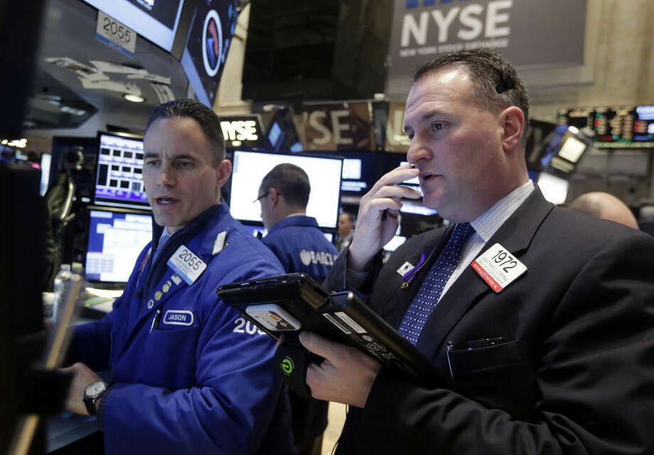 Specialist Jason Hardzewicz, left, and trader Jonathan Corpina worknon the floor of the New York Stock Exchange Wednesday, Jan. 21, 2015. The U.S. stock market is mixed in early trading after two straight days of gains. (AP Photo/Richard Drew)