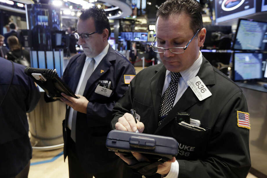 Trader Edward Curran, right, works on the floor of the New York Stock Exchange Wednesday, Jan. 21, 2015. The U.S. stock market is mixed in early trading after two straight days of gains. (AP Photo/Richard Drew)