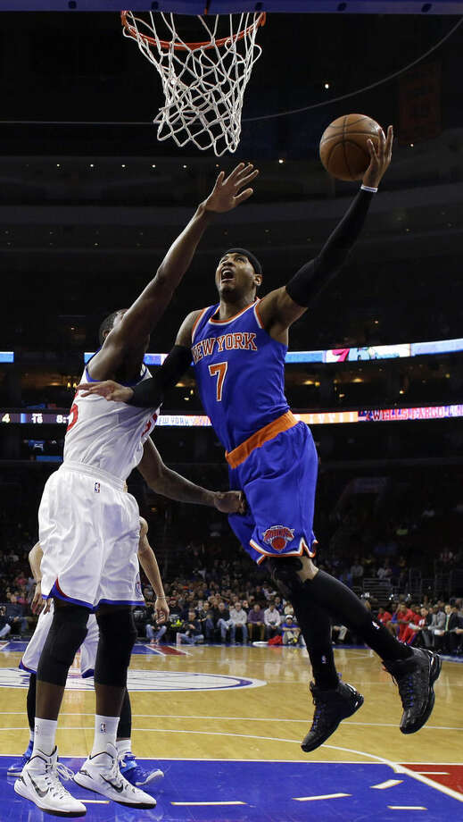 New York Knicks' Carmelo Anthony, right, goes up for a shot against Philadelphia 76ers' Henry Sims during the first half of an NBA basketball game, Wednesday, Jan. 21, 2015, in Philadelphia. (AP Photo/Matt Slocum)