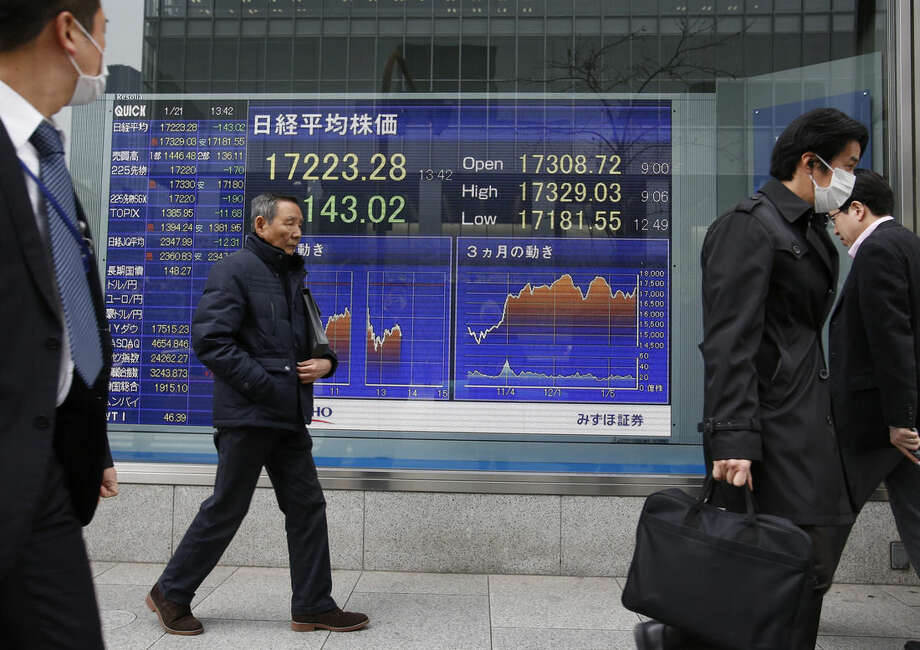 People walk past an electronic stock indicator of a securities firm in Tokyo Wednesday, Jan. 21, 2015. Most Asian stock markets rose Wednesday as investors anticipated European policymakers would soon unleash more stimulus while Chinese shares extended their rebound following a steep plunge at the start of the week. (AP Photo/Shizuo Kambayashi)