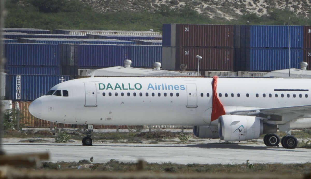 The Daallo Airlines plane that was forced to make an emergency landing late Tuesday, sits in the airport in Mogadishu, Somalia Wednesday, Feb. 3, 2016. The pilot described on Wednesday how the crew jumped into action to fly the plane back to Mogadishu airport and keep the passengers calm even as smoke enveloped the passenger cabin and wind rushed through a hole blown through the fuselage. (AP Photo/Farah Abdi Warsameh)