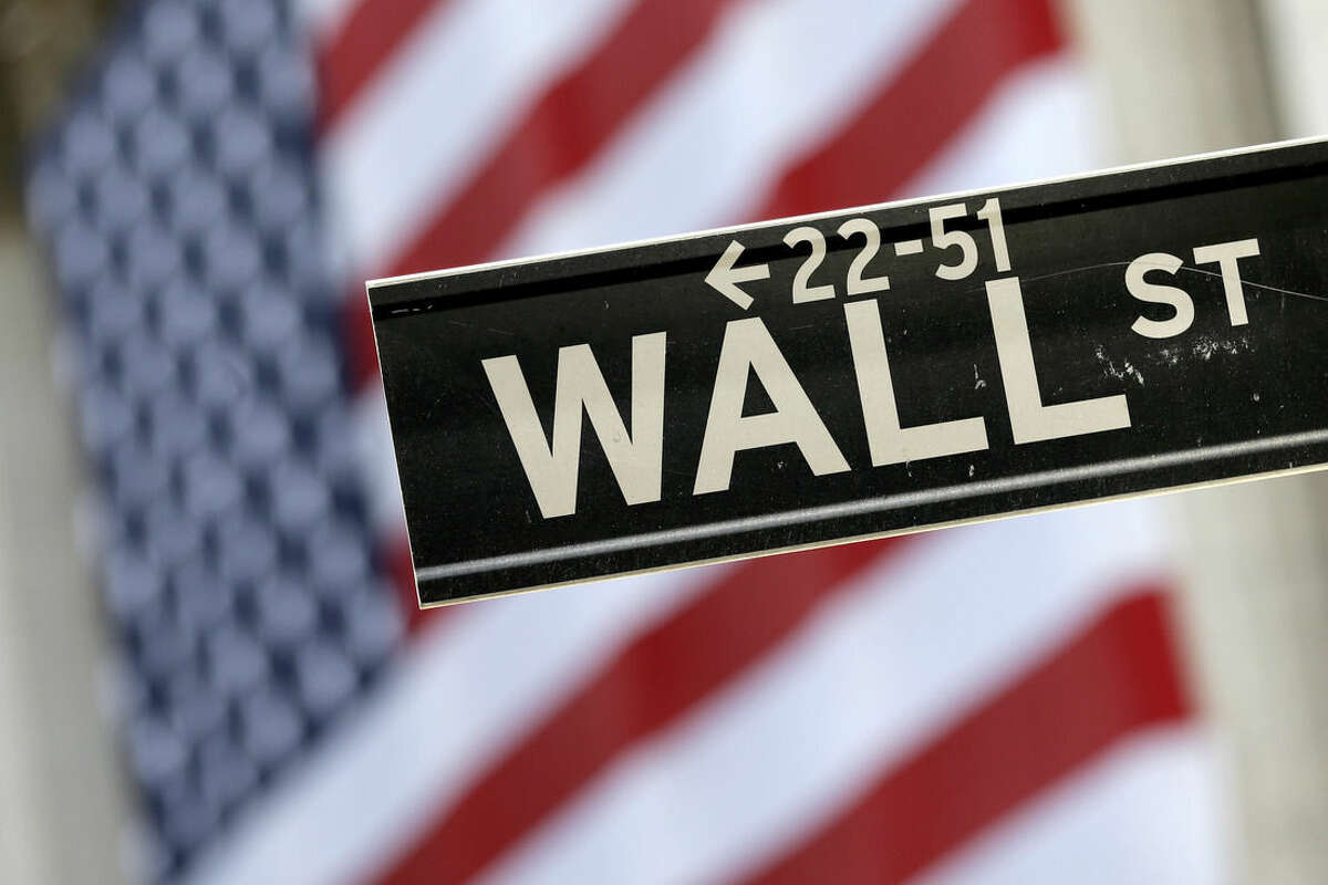 FILE - In this Sept. 8, 2015, file photo, a Wall Street street sign is framed by a giant American flag hanging on the facade of the New York Stock Exchange. European stock markets recovered their poise Tuesday, Sept. 29, 2015, despite an earlier rout in Asia which featured a 4 percent slide in Japan's main index. (AP Photo/Mary Altaffer, File)