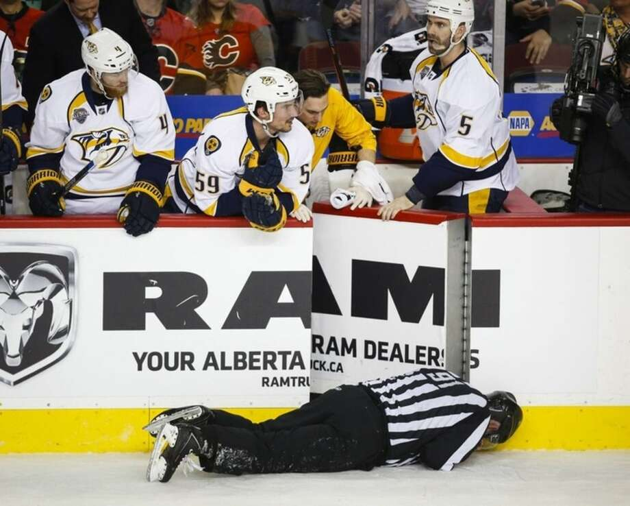 Nashville Predators' players look over the bench at linesman Don Henderson after he was hit by Calgary Flames' Dennis Wideman during second period NHL hockey action in Calgary, Alberta, Wednesday, Jan. 27, 2016. (Jeff McIntosh/The Canadian Press via AP)