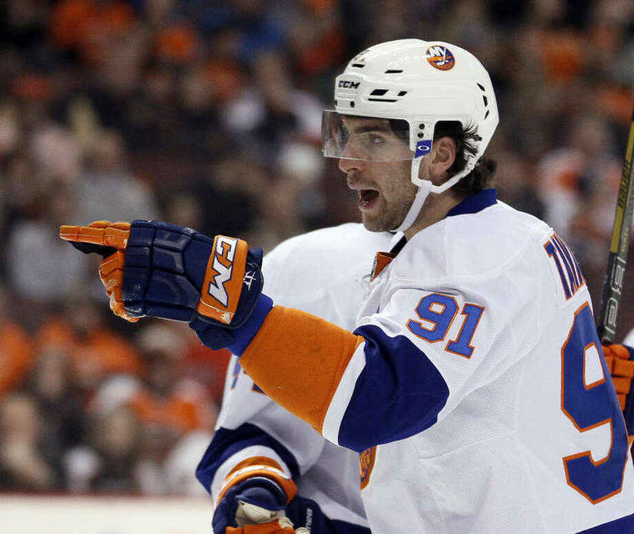 New York Islanders' John Tavares points towards Thomas Vanek, not pictured, who got the assist on Tavares' goal during the first period of an NHL hockey game with the Philadelphia Flyers, Saturday, Jan. 18, 2014, in Philadelphia. (AP Photo/Tom Mihalek)