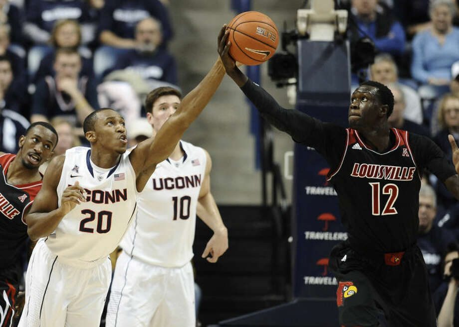 Connecticut's Lasan Kromah (20) and Louisville's Mangok Mathiang (12) reach for a loose ball during the first half of an NCAA college basketball game, Saturday, Jan. 18, 2014, in Storrs, Conn. (AP Photo/Jessica Hill)