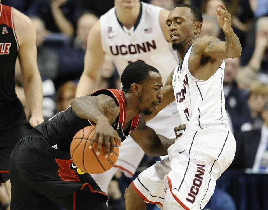 Louisville's Russ Smith, left, drives to the basket as Connecticut's Ryan Boatright, right, defends during the first half of an NCAA college basketball game, Saturday, Jan. 18, 2014, in Storrs, Conn. (AP Photo/Jessica Hill)